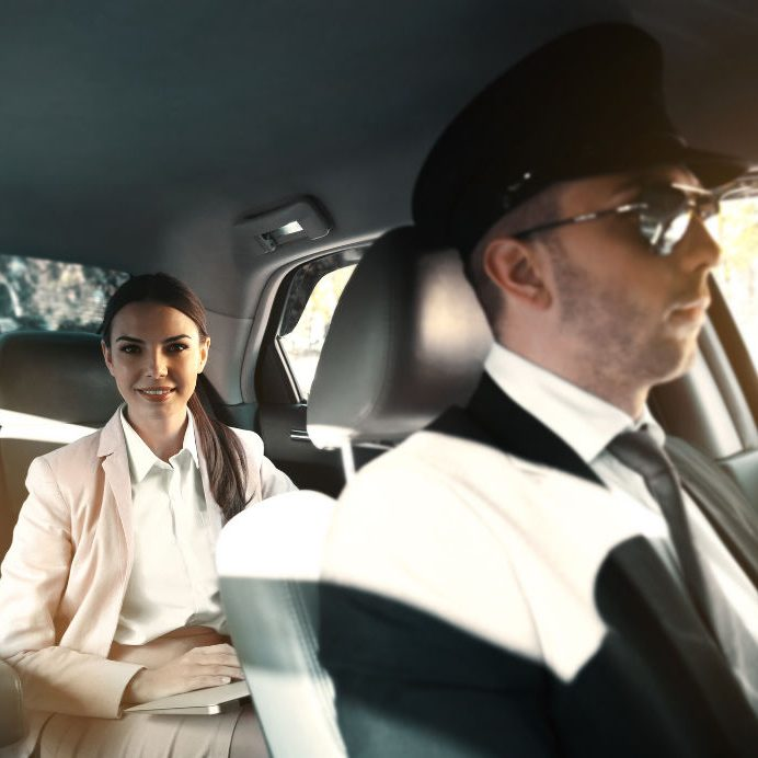 Businesswoman riding a car with chauffeur